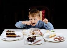 Śliczna chłopiec cieszy się fundę partyjni torty Zdjęcie Royalty Free