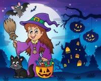 Śliczna czarownica i kot w Halloweenowej scenerii Zdjęcia Stock