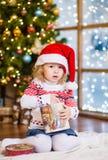 Śliczna dziewczyna w czerwonym Santa kapeluszowym obsiadaniu z czerwonym kapeluszem Zdjęcia Stock
