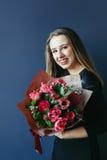 Śliczna dziewczyna z bukietem czerwoni tulipany Obrazy Stock