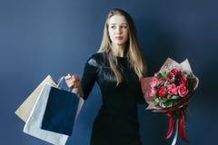 Śliczna dziewczyna z bukietem czerwoni tulipany i pakunki Fotografia Stock