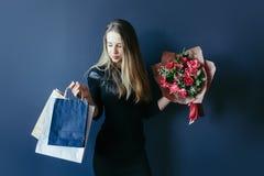 Śliczna dziewczyna z bukietem czerwoni tulipany i pakunki Obrazy Stock