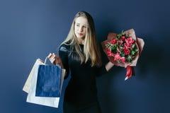 Śliczna dziewczyna z bukietem czerwoni tulipany i pakunki Fotografia Royalty Free