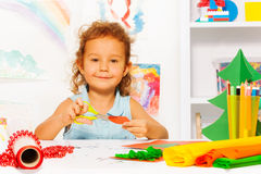 Śliczna dziewczyna z nożycami i papierem siedzi przy biurkiem Fotografia Royalty Free