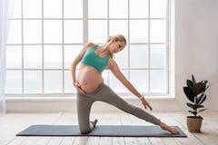 Śliczna expectant kobieta w sportswear robi joga Zdjęcia Stock