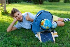Śliczna, mądrze, młoda chłopiec w błękitnej koszula, siedzi na trawie obok jego szkolnego plecaka, kula ziemska, chalkboard, work fotografia royalty free