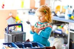 ?liczna ma?a berbe? dziewczyna pomaga w kuchni z naczynie pralk? Szcz??liwy zdrowy blondynki dziecko sortuje no?e zdjęcia royalty free