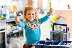 ?liczna ma?a berbe? dziewczyna pomaga w kuchni z naczynie pralk? Szcz??liwy zdrowy blondynki dziecko sortuje no?e obraz royalty free