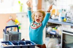 ?liczna ma?a berbe? dziewczyna pomaga w kuchni z naczynie pralk? Szcz??liwy zdrowy blondynki dziecko sortuje no?e fotografia stock