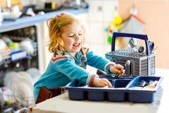 ?liczna ma?a berbe? dziewczyna pomaga w kuchni z naczynie pralk? Szcz??liwy zdrowy blondynki dziecko sortuje no?e zdjęcie stock