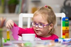 ?liczna ma?a dziewczynka robi preschool malowa? i pracie domowej zdjęcia stock