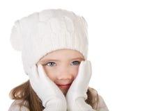 Śliczna mała dziewczynka w ciepłym kapeluszu i rękawiczkach zamyka jej cheks isolat Zdjęcie Royalty Free