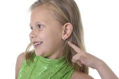 Śliczna mała dziewczynka wskazuje jej ucho w częściach ciała uczy się szkolnego mapy seria Zdjęcia Royalty Free