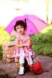 Śliczna mała piękna dziewczyna z różowym parasolem i torebką w parku Obrazy Stock