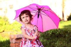 Śliczna mała piękna dziewczyna z różowym parasolem i torebką w parku Obraz Stock