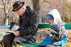 Śliczna młoda chłopiec czyta ebook na pastylce Obrazy Stock