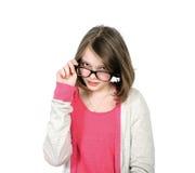 Śliczna młoda dziewczyna patrzeje nad jego szkłami przeglądać Zdjęcie Royalty Free