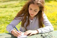 ?liczna nastoletnia dziewczyna pisze notatkach na papierowym ochraniaczu drewnianym sto?em na zielonej ??ce zdjęcie royalty free