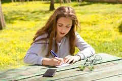?liczna nastoletnia dziewczyna pisze notatkach na papierowym ochraniaczu drewnianym sto?em na zielonej ??ce zdjęcia royalty free