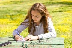?liczna nastoletnia dziewczyna pisze notatkach na papierowym ochraniaczu drewnianym sto?em na zielonej ??ce fotografia royalty free
