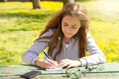 ?liczna nastoletnia dziewczyna pisze notatkach na papierowym ochraniaczu drewnianym sto?em na zielonej ??ce obraz stock