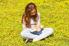 ?liczna nastoletnia dziewczyna pisze notatkach na papierowym ochraniaczu na zielonej ??ce Selekcyjna ostro?? obrazy royalty free