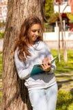 ?liczna nastoletnia dziewczyna pisze z pi?rem blisko w notatniku w parku Selekcyjna ostro?? zdjęcia stock