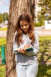 ?liczna nastoletnia dziewczyna pisze z pi?rem blisko w notatniku w parku Selekcyjna ostro?? zdjęcie royalty free