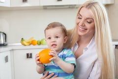 Śliczna rodzina je owoc w kuchni Obrazy Royalty Free