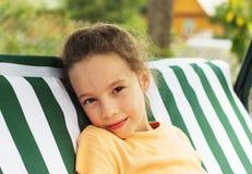 Śliczna smutna szkolna dziewczyna jest odpoczynkowa przeciw zieleni lato park Fotografia Stock