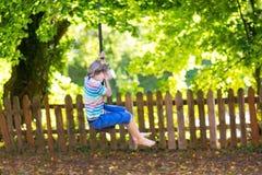 Śliczna szkolna chłopiec cieszy się huśtawkową przejażdżkę na boisku Obrazy Royalty Free
