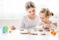 Śliczne dziewczyny dekoruje Wielkanocnych ciastka Obrazy Royalty Free