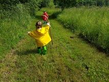 Śliczni berbecie biega na rolnej drodze z kijem Zdjęcie Stock