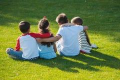 Śliczni dzieciaki siedzi obejmowanie na zielonej trawie w parku Fotografia Stock