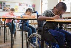 Śliczni ucznie pisze przy biurkami w sala lekcyjnej Zdjęcia Royalty Free