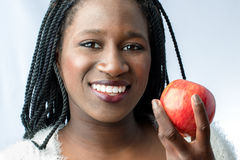 Śliczny afrykański nastoletni z powabnym uśmiechu mienia czerwieni jabłkiem Zdjęcie Royalty Free