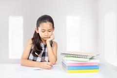 Śliczny azjatykci dzieciaka koncentrat na jej pracie domowej Zdjęcia Stock