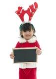 Śliczny azjatykci dziecko jest ubranym Santa mienia kostiumowego blackboard Obraz Stock
