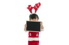Śliczny azjatykci dziecko jest ubranym Santa mienia kostiumowego blackboard Zdjęcia Stock