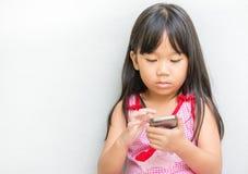 Śliczny azjatykci dziewczyna zegarka film na telefonie komórkowym Zdjęcia Royalty Free