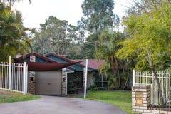 Śliczny ceglany australijczyka dom z dachówkowym dachem i markiza tulonym plecy w tropikalnego tropikalnego las deszczowego zdjęcia stock
