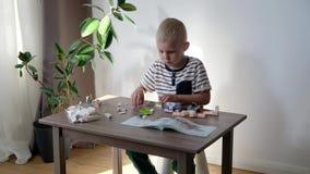 ?liczny ch?opiec 6 lat bawi? si? z kolorowymi klingeryt zabawki ceg?ami przy sto?em w domu zbiory