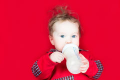 Śliczny dziecko pije mleko na czerwonej koc Obrazy Royalty Free