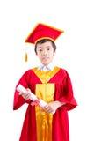 Śliczny Little Boy Jest ubranym Czerwonego toga dzieciaka skalowanie Z Mortarboard Fotografia Stock