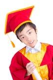 Śliczny Little Boy Jest ubranym Czerwonego toga dzieciaka skalowanie Z Mortarboard Zdjęcie Royalty Free