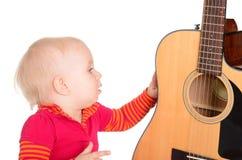 Śliczny mały muzyk bawić się gitarę odizolowywającą na białym tle Zdjęcia Stock