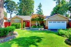 Śliczny mały rambler dom z czerwonym drzwi i biel garażujemy drzwi Zdjęcie Stock