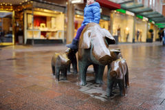 Śliczny mały turystyczny obsiadanie na popularnej rzeźbie świniowata rodzina, swineherd i jego pies w Bremen, Zdjęcia Royalty Free