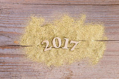 Liczy 2017 na drewnianym tle z złotą błyskotliwością Obrazy Stock