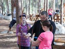 Lid van de jaarlijkse wederopbouw van het leven van de Vikingen - ` Viking Village ` onderwijst bezoekers hoe te om pijlen in het Royalty-vrije Stock Foto's